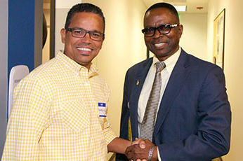 DeVry Orlando Campus Dean, Abel Okagbre, and DeVry alum, Luis Gomez, shaking hands at an Alumni Association event.